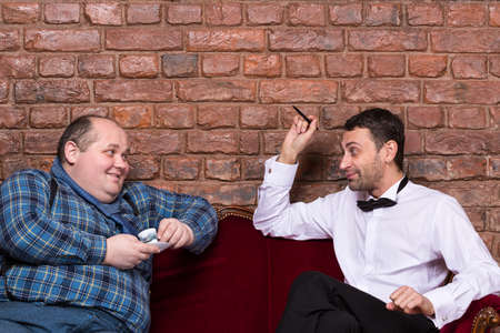Elegant man sitting with an overweight country yokel