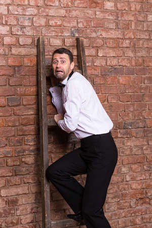 panicky: Terrified man trapped at the top of a ladder cowering against the brick wall with an expression or dread and fear