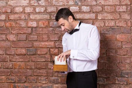oud document: Mens die zich een oud document van een houten doos die hij houdt in zijn hand lezen tijdens het staan voor een bakstenen muur
