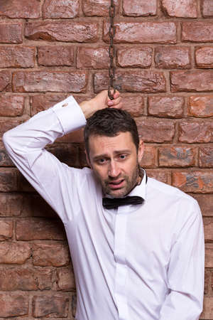 disconsolate: Conceptual image of a desperate handsome businessman in a bow tie standing against a brick wall with a chain around his neck and a disconsolate depressed expression Stock Photo