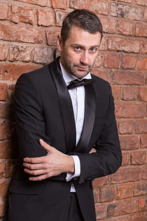 sultry: Elegant handsome macho man in a bow tie and tuxedo leaning against a brick wall giving the camera a sultry look