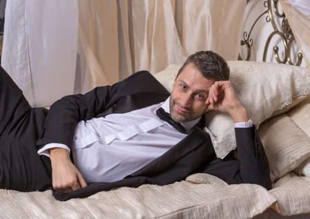 gigolo: Elegant handsome playboy in a bow tie and suit reclining on a bed in an elaborate bedroom with a seductive smile on his face Stock Photo