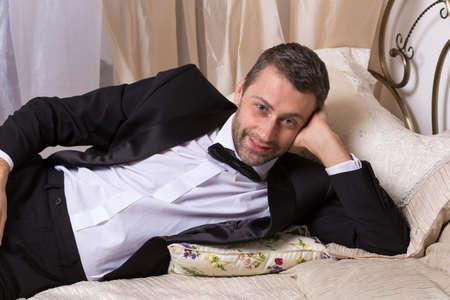 playboy: Elegante knappe playboy in een vlinderdas en pak liggend op een bed in een uitgebreide slaapkamer met een verleidelijke glimlach op zijn gezicht Stockfoto