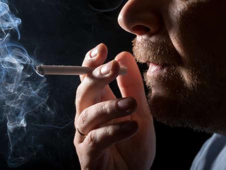 Portrait man smoking cigarette, closeup on black background photo