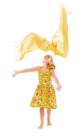 jolie fille: Little Girl dans une robe jaune jette vers le haut Ch�le, sur fond blanc
