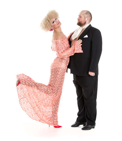 výstřední: Eccentric Fat Man in a Tuxedo and Beautiful Lady in an Evening Dress, drag queen artists on white background