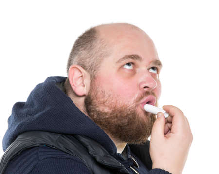 fatso: Bald Bearded Fat Man Uses a Protective Lipstick, on white background