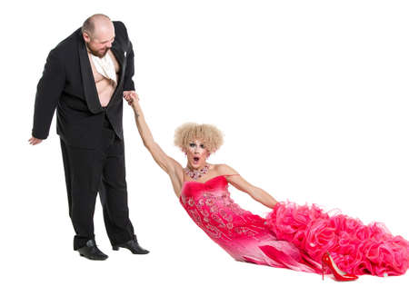 dragging: Eccentric Fat Man Dragging a Woman by the Hand Lying on Floor, drag queen artists on white background Stock Photo