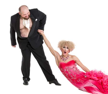 uomo rosso: Eccentrico Fat Man Trascinando una donna per mano Sdraiato sul pavimento, trascinare artisti regina su sfondo bianco Archivio Fotografico
