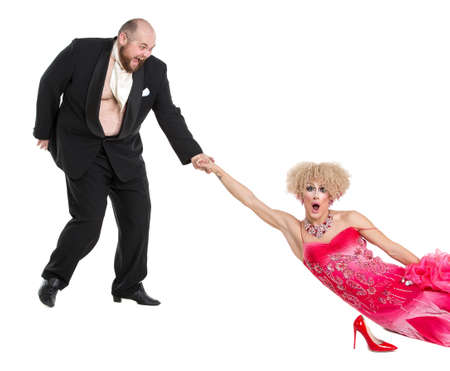 fatso: Eccentric Fat Man Dragging a Woman by the Hand Lying on Floor, drag queen artists on white background Stock Photo
