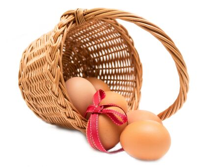 Easter egg wioth red ribbon in a basket isolated on a white background Фото со стока