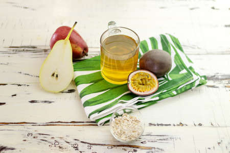 Still life with tea, pear, oats and passion fruit. Top view. On a beautiful vintage table with a modern print towel.