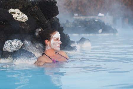 personas banandose: Mujer de relax en el spa geotérmica en la piscina de aguas termales en Islandia. Muchacha que disfruta de baño en una laguna de agua azul con el famoso barro curativo en su cara.