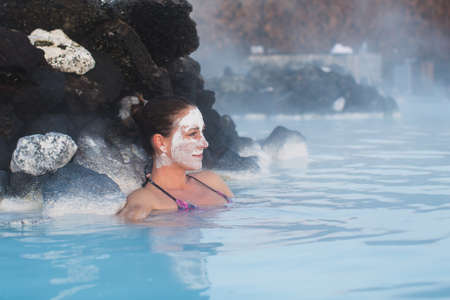 tourism: Woman relaxing in geothermal spa in hot spring pool in Iceland. Girl enjoying bathing in a blue water lagoon with famous healing mud on her face.