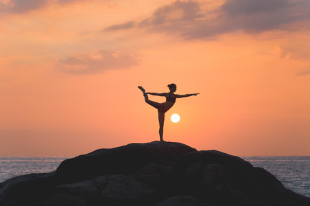 Warrior pose from yoga by woman silhouette on sunset