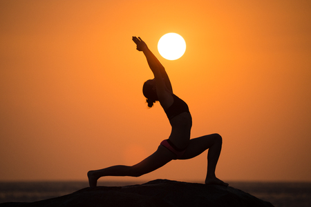 woman pose: Warrior pose from yoga by woman silhouette on sunset