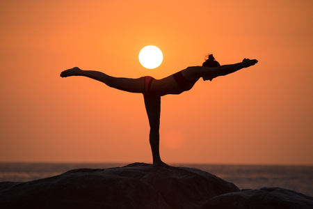 guerrero: Guerrero pose de yoga por la silueta de la mujer en la puesta del sol