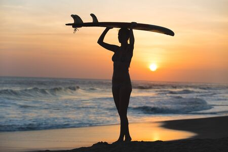 rear view girl: Beautiful young surfer girl in bikini with surfboard on a beach