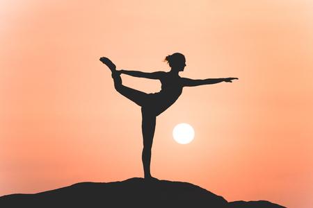 Guerrero pose de yoga por la silueta de la mujer en la puesta del sol Foto de archivo - 46492464