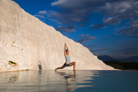 vriksasana: Warrior pose from yoga by woman silhouette on sunset in Pamukkale, Turkey Stock Photo