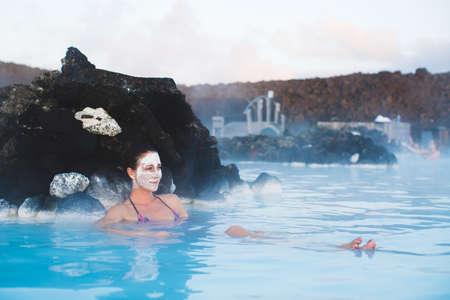 blue lagoon: Donna che si distende nella stazione termale geotermica in piscina termale in Islanda. Ragazza che gode il bagno in una laguna di acqua blu con il famoso fango curativo sul viso. Archivio Fotografico