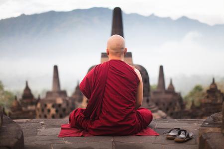Monk in the famous Borobudur Buddhist temple meditate on sunrise
