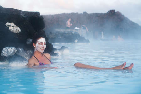 mujer ba�andose: Woman close eyes and relaxing in geothermal spa in hot spring pool in Iceland. Girl smile and enjoying bathing in a blue water lagoon with famous healing mud on her face. Foto de archivo