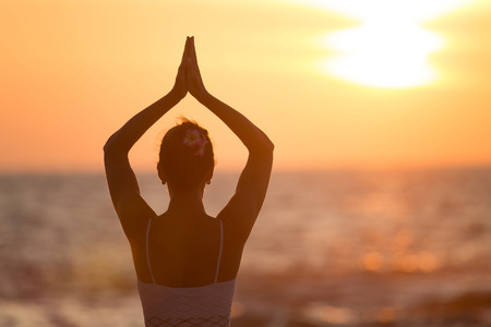 yoga: Vrikshasana tree pose from yoga by woman silhouette on sunset