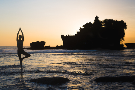 Vrikshasana tree pose from yoga by woman silhouette on sunset near Tanah lot temple 스톡 콘텐츠