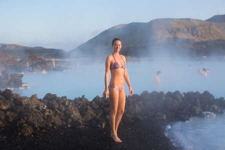 therapy geothermal: Woman relaxing in geothermal spa in hot spring pool in Iceland. Girl enjoying bathing in a blue water lagoon with famous healing mud on her face.