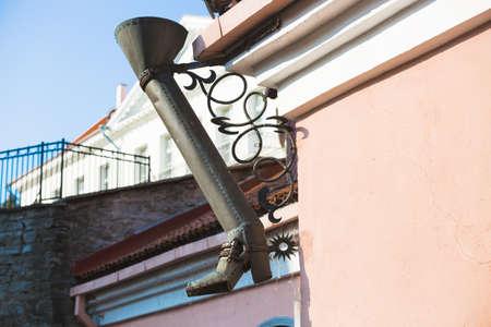 Boot like downtake tube in street of old town in Tallinn, Estonia
