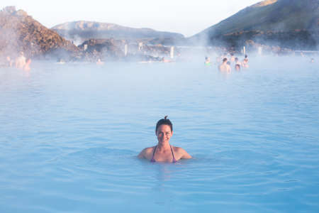 therapy geothermal: Woman relaxing in geothermal spa in hot spring pool in Iceland. Girl enjoying bathing in a blue water lagoon with famous healing mud. Stock Photo