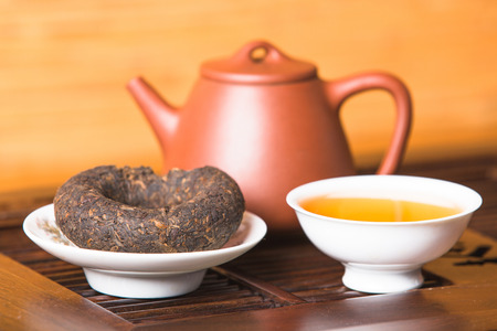 Chinese tea set and pu-erh tea cake on the tray, Closeup.