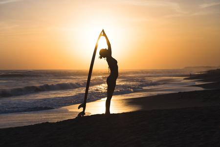 해변에서 서핑 보드와 비키니 입은 아름 다운 젊은 써 퍼 야 소녀