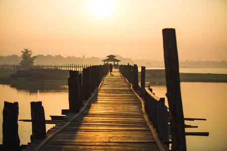 People walk on U Bein bridge at sunrise