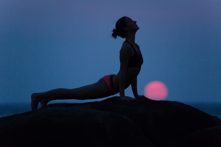 Pose from yoga by woman silhouette with the first light of rising sun