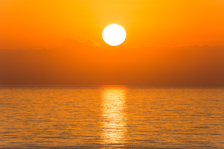 Sun disk with reflection in the ocean at sunrise in Florida, Aventura Beach