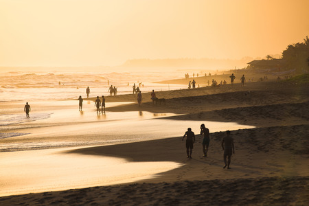 Silhouettes of people at sunset on Kuta beach in Bali, Indonesia