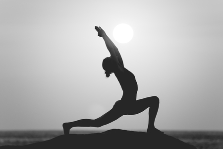 Warrior pose from yoga by woman silhouette on sunset black and white style filter