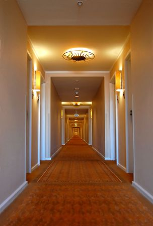 Looking down a long hotel corridor photo