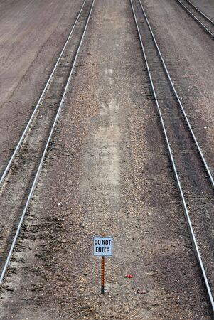 Do Not Enter sign between railroad tracks photo