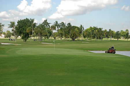 Landscaper mowing the grass on a golf course, Miami, Florida Stockfoto