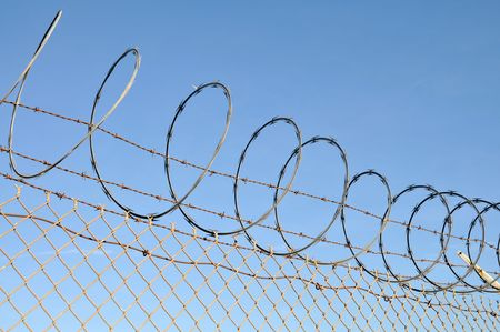 Security fence topped with barbed and razor wire