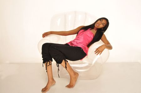 sprawled: Largo pelo, de piel oscura belleza sprawled en una silla invisible