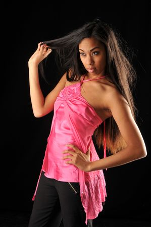 Long haired, dark skinned beauty against a black background