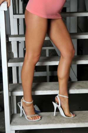 Long legs and a very short skirt on a stairway Stock Photo