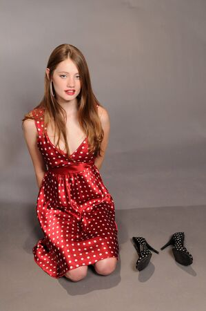 kneeling woman: Auburn haired beauty in red polka dots kneeling on the floor