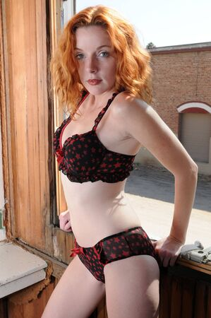 Beautiful redhead in black and red lingerie at an open window