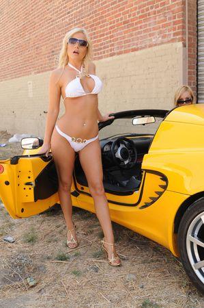 Beautiful blonde in a white bikini standing in the door of a yellow sportscar