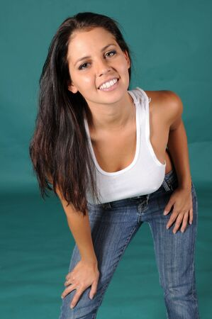 Beautiful brunette in a cropped white top and jeans photo